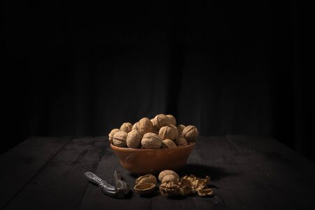 Walnuts in a bowl on dark background. Low-key image of nuts on black rustic table, artistic light and shadow technique and copys pace