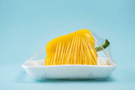 Yellow bell pepper wrapped in plastic clingfilm in blue background. Recycling and environment concept: fresh food in plastic package