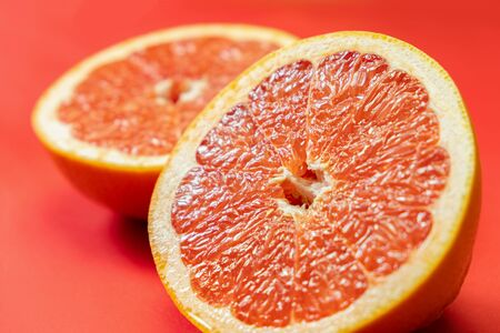 Grapefruit cut in half on vivid red background. Fruitarianism, vegetarian or vegan food: close-up view of fresh and ripe citrus fruit in bright colors