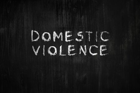 Domestic violence phrase handwritten on black wood background. Sign, concept of dealing with behaviour toxic relationship at home or in society