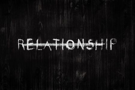 """Relationship word crossed out on black wood background. Sign, concept of dealing with personal issues - the word """"relationship"""" on a blackboard"""