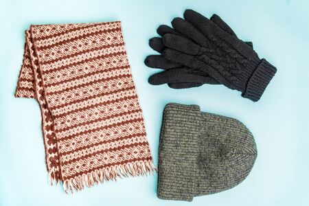 Top view of winter clothing accessories for outdoor use. Knit-hat beanie, winter gloves and wool scarf neatly organised on pale blue background