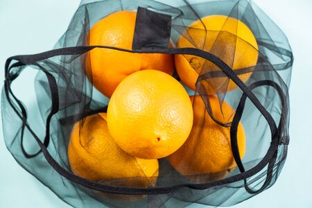Top view of oranges in a reusable string bag. Sustainable eco packaging concept: shopping for groceries with a multi-use bag to reduce ecological footprint