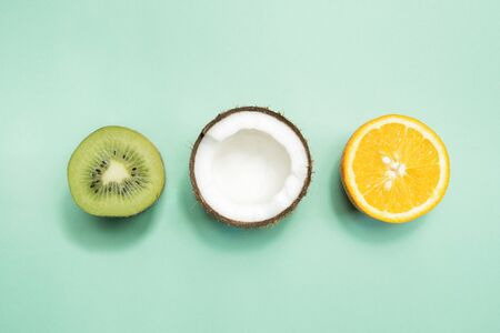 Kiwi fruit, coconut and orange on green background. Concept of fruitarianism, vegetarianism, veganism, natural vitamins and health.