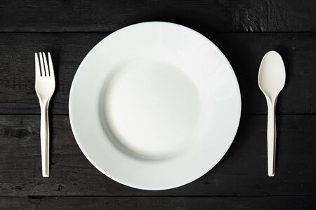 Empty white bowl, fork and spoon on black wood table, close-up view. Diet concept: flat lay of clean kitchen dishes on dark rustic background