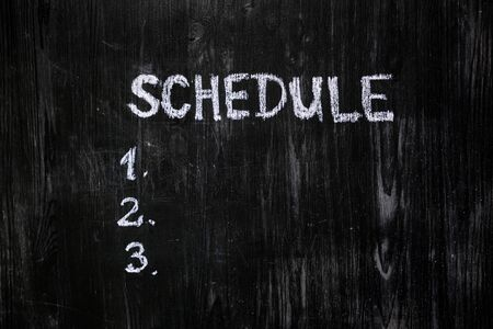 Schedule list handwritten with chalk on blackboard. Black wood background and a list of scheduled tasks to do, top view. Time management concept. Foto de archivo