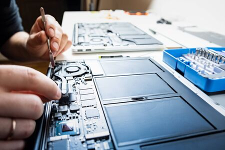 Cleaning a laptop at a professional service. Person performs regular service and changes thermal grease of modern portable computers, selective focus