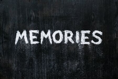 """Mental issues concept: hand written word """"memories"""" crumbling on black wood background. Top view of a phrase on a blackboard associated with memory decline, old age Archivio Fotografico"""