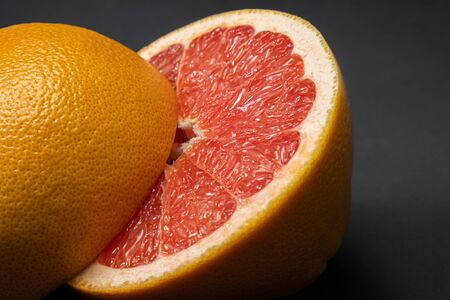 Grapefruit cut in half on dark low-key background, copy space. Fruitarianism, vegetarian or vegan food: close-up view of fresh and ripe citrus fruit in faded colors