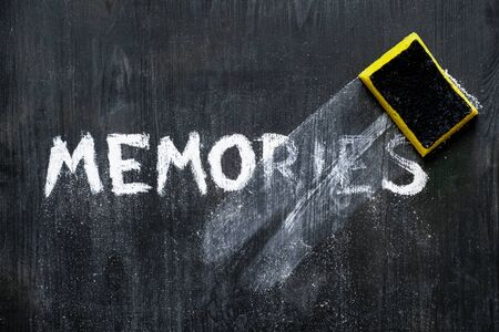 """Mental issues concept: hand written word """"memories"""" wiped off the black wood background. Top view of a crumbling phrase on a blackboard associated with memory decline, old age"""