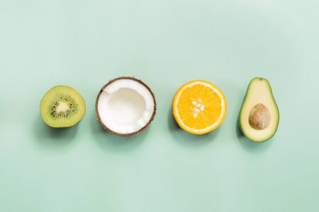 Kiwi fruit, coconut, orange and avocado on green background. Concept of fruitarianism, vegetarianism, veganism, natural vitamins and health. Banco de Imagens
