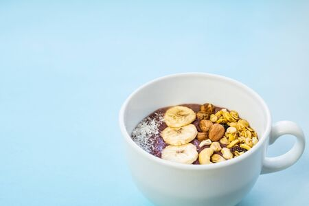 Bowl of fruit smoothie with nuts and banana slices. Acai bowl with cereals, cashews and hazelnuts in blue bright background