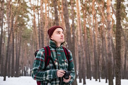 Hiking male person in winter forest taking photographs. Man in checkered winter shirt in beautiful snowy woods with an old film camera