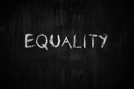 """Equality word handwritten on black wood background. Sign, concept of dealing with social issues - the word """"equality"""" on a blackboard"""