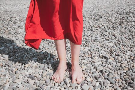 Standing on the pebble by the sea, concept of summer vacation and rest. Woman in bright red dress at the seaside Reklamní fotografie