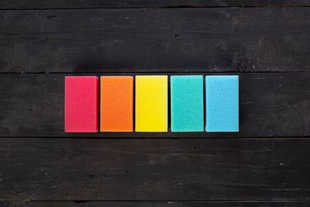 Sponges of different colors in dark background, top view. Five pieces of dishcloth laid in row on dark background, shot from above