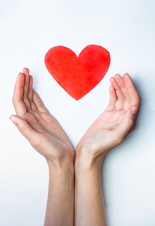 Heart sign drawn with a marker pen and hands embracing it. Concept of love, care and peace: shape of a heart resting safely in human palms.