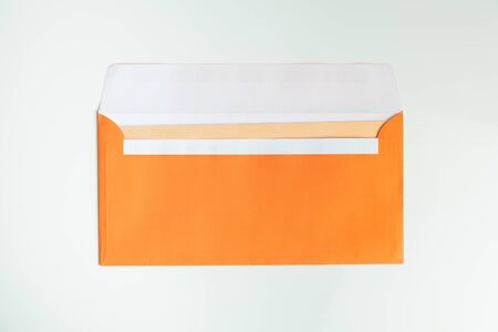 Orange envelope in white background, top view. Abstract image of postal package, concept of communication and mailing