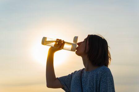 在日落的天空背景下,一个年轻的女人喝着瓶子里的水。日落时拿着可重复使用的水瓶的女性肖像,口渴和补水概念