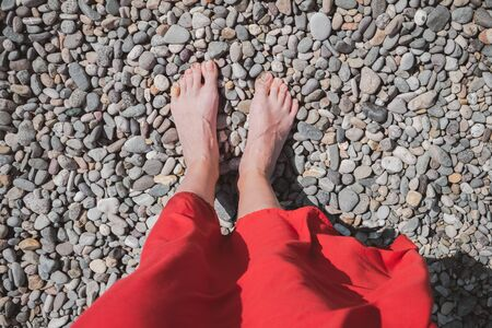 Standing on the pebble by the sea, concept of summer vacation and rest. Woman in bright red dress at the seaside, point of view shot Reklamní fotografie