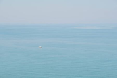 Calm blue sea fusing with skies.  Peaceful and tranquil marine view, a small boat passing by. Reklamní fotografie