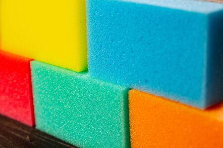 Sponges of different colors in dark background forming a wall. Pieces of dishcloth laid as bricks on dark background Stock Photo
