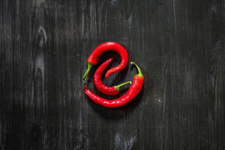 Three chili peppers on black background, top view. Sparse flat lay of red hot peppers forming a circle on a dark wood table