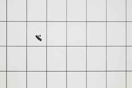 Surveilance camera on the wall in geometric pattern background. Security camera in minimalistic urban surrounding, concept of watching over