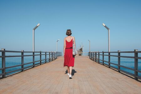 Walking along the pier by the blue sea. Woman in red dress goes along the quay. shot from behind