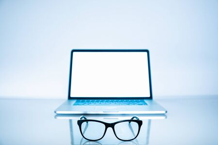 Computer eyeglasses in front of a laptop, close-up view. Blue light blockers and laptop in bright background, eye fatique problem concept