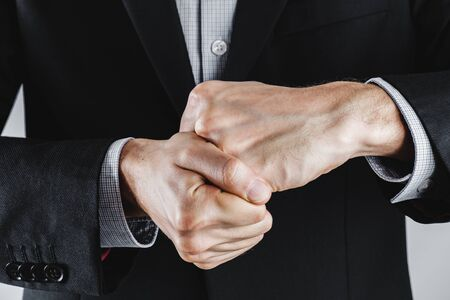 Human hands held in fists - struggle, agression or anger in business. Concept of hard competition, violence or rivalry at work