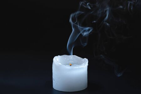 Smoke rising from a dipped candle. Blue smoke of a candle in dark background, concept of air pollution from oil products burning