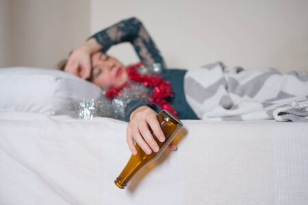Woman in bed suffering from hangover after a loud party. Drunk sleeping at a crash pad concept: young female resting after a celebration