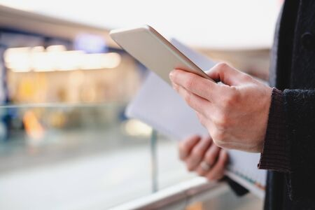 Human hands hold a tablet or e-book at a public place, close-up view. Web browsing, using technology on the go at the shopping mall, airport or food courts, shallow depth of field image in high key