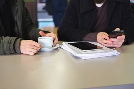 Business or partner negotiation out of office concept: hands of two busy people on the table. A person with smartphone and heap of documents together with a man having a cup of coffee sit together at a public place Stock Photo