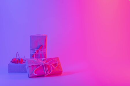 Handmade gifts wrapped in paper package in bright neon lights. Three presents in vivid blue red purple background