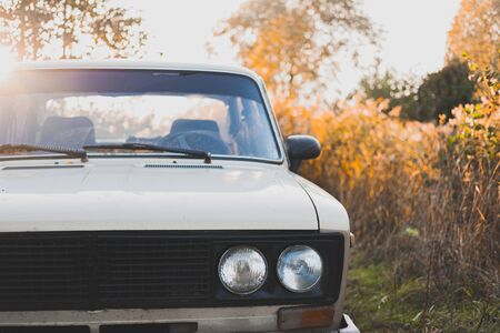Old soviet car in sunset, detailed front view. Retro aesthetics concept, old vehicle among beautiful autumn plants