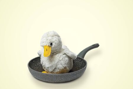Cute fluffy toy chicken on a frying pan. Cruel meat industry, poultry consumption concept
