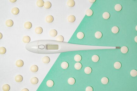 Electronic medical thermometer among yellow pills in two color background. Health issues, being cold, doing home treatment or having fever concept Stock Photo