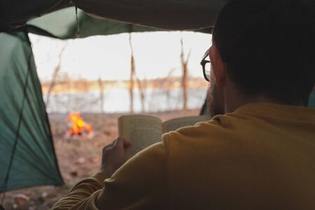 Man sits in tent by the campfire and reads a book. Enjoying quiet peaceful holiday on the nature, the concept of tranquility and getting away from urban noise and technology