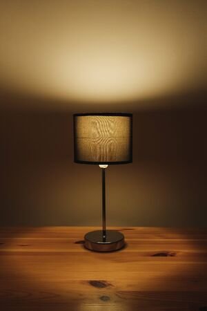 Electric lamp on the table top, natural low key light. Cozy bedroom light at night, minimalistic and sparse image