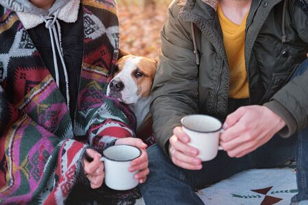 Two people and their funny dog having a lovely time outdoors. Man and woman in warm clothes sit outdoors together with their pet on a lovely chilly day Stock Photo