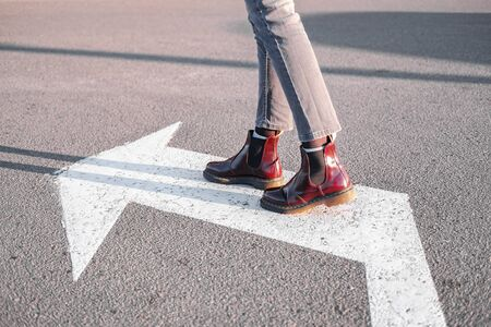 Feet walking along the left turn sign. Concept of making correct decisions, changing direction or attitude in life
