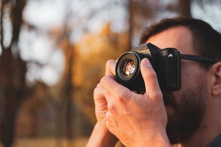 Male photographer with a vintahe film camera. Man taking a photo in a beautiful autumn background Stock Photo