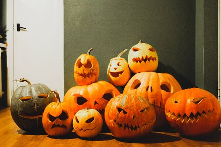 Carved halloween pumpkins on green background. Halloween concept: pile of jack o'lantern pumpkins with scary faces