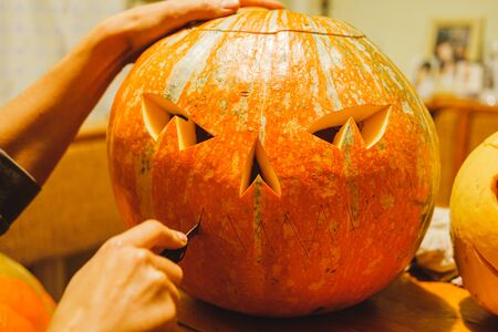 Carving a halloween pumpkins in the kitchen, close-up view. Marking and carving large jack o'lantern pumpkins