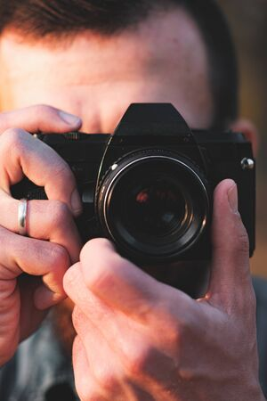 Close-up view of a black SLR camera in hands. Male photographer holds a vintage photocamera