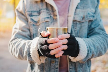 Man in mittens keeps warm holding a cup of hot drink. Chilly morning outdoors scene: human hands with a tin cup of hot beverage