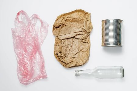 Different types of recyclable garbage. Plastic bag, paper bag, tin can and glass bottle on white background