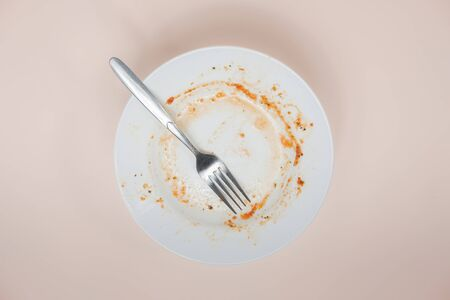 A plate with rests of tomato sauce in it, top view. Unwashed dishes illusatration, filthy plate on light background